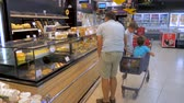 ATHENS, GREECE - JULY 10 2019: Shopping background. Children sitting in shopping cart. Father moving around supermarket with two kids sitting in shopping cart. Choosing products at supermarket. Food Стоковые видеозаписи