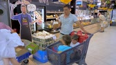 ATHENS, GREECE - JULY 10 2019: Father driving sons in shopping cart along the supermarket. Two boys sitting in the shopping cart with products on it. Making decision which products to choose buy. Стоковые видеозаписи