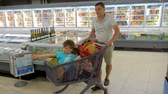 ATHENS, GREECE - JULY 10 2019: Father driving sons in shopping cart along the supermarket. Father at supermarket with two cute little sons sitting in shopping cart. Making decision which products.