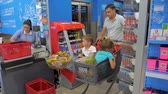ATHENS, GREECE - JULY 10 2019: Joyful loving father having fun in supermarket with two cute little sons, he is going with shopping cart with small boys sitting in it. Shopping background. Стоковые видеозаписи