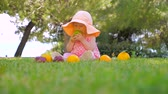 backyard : Natural fruits background. Kid eating organic fruits outdoor. Toddler playing with fresh fruits on green grass on sunny summer day. Baby on green backyard near see shore. Baby sitting on green grass