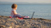 concettuale : Toddler sitting with notebook on seashore. New generation of people who combine work and vacation. Preschool background. Revolution in education. Developing creativity. New education system background