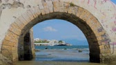 Stone bridge through Mediterranean sea with cityscape on background. Travel background. Special place of European tourism. Mediterranean sea with different color of water. Dostupné videozáznamy