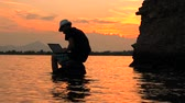 Programmer with notebook sitting on the rock in the sea on sunset background. Freelancer working on the nature. Distant job background. New approach to job search. Your favourite job