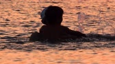 Parent and son in the sea with sunset reflecting in the water. Family tours, trips. Travel to Europe. Summer vacation background. Travel trend concept. Original travel. Unique places, locations Videos
