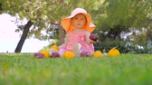 Little princess playing with fruits outdoor. Child in panama having fun outdoor on back yard. Happy childhood concept. Toddler sitting on green grass waiting for mother. Archivo de Video