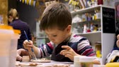 Art school. Boy decorate gift with paintbrush. Drawing lesson. Art workshop. Little painter. Boy decorating clay product with great interest. Leisure activity for child. Kid preparing present.