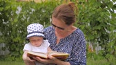 Reading concept. Woman holding book behind baby girl. Little girl looking into open book. Open book in womans hands. Toddler with mother reads the book. Close-up. American girl in panama