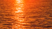 Scenic seascape with sunset reflecting in seawater. Passer-by with notebook walking past. Hot magma color palette. Unusual seascape during sunset. Seawater reflects sunset. Reflected sun in seawater Stock mozgókép