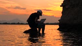 Happy man sitting on the stone and working at computer with sea view, static frame. Male silhouette on sunset seascape background. Travel blogger working on seaside. Freelancer concept. Videos