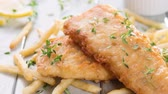fish and chips : Fish and chips. Fried fish fillet with French fries on bright wooden background. 4k footage side panning. Stock Footage