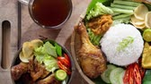 malaio : Famous traditional Indonesian food. Delicious nasi ayam penyet with sambal belacan. Fried chicken rice and tea with overhead view. 4k footage video.