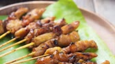 raya : Close up chicken satay on wooden dining table, one of famous local dishes. 4k footage video. Stock Footage