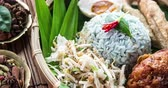 cusine : Nasi kerabu or nasi ulam, popular Malay rice dish. Blue color of rice resulting from the petals of butterfly-pea flowers. Traditional Malaysian food, Asian cuisine, 4k footage video. Stock Footage
