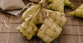 raya : Ketupat (rice dumpling) is a local delicacy during the festive season in South East Asia. Ketupat, a natural rice casing made from young coconut leaves for cooking rice on traditional mat background. 4k footage video.