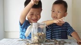 Slow motion children drops coin money into glass jar, financial concept.