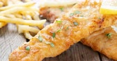 Fish and chips. Fried fish fillet with French fries on bright wooden background. 4k footage side panning. 動画素材