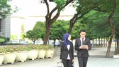 Business people walking and discussing, using tablet pc outdoor. 動画素材