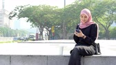 Muslim woman using smartphone and laughing alone.