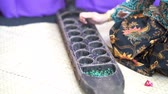 Woman hand playing congkak, traditional Malay two player game in which seeds or marbles are dropped into depressions carved into a boat-shaped wooden board. 動画素材