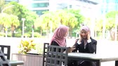 Muslim office woman having headache, sitting outdoor.