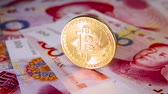 Financial concept with golden Bitcoin over chinese yuan bill