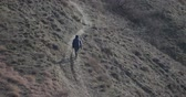 hiking trail : woman climbs the path in the mountains