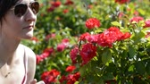 малиновый : Young woman with sunglasses smelling red flowers in a sunny day