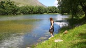 magyarázza : A young girl in a dress dissatisfied explains on the shore of a mountain lake