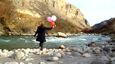 kamie�� : Happy woman with balloons walking on the river bank