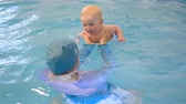 おむつ : the trainer teaches the kid to swim in the pool