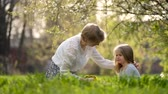 mother with a short haircut and a little girl sitting in the bright green spring grass. slow motion Vídeos