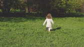 A little girl in a dress runs away from the camera on the green grass.