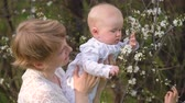 Mom with a short haircut, with a baby in her arms, looking at a flowering tree