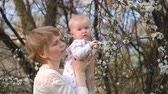 ser : Mom with a short haircut, with a baby in her arms, looking at a flowering tree
