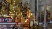 icon : Golden buddha statue and Chinese god statue for worship at chinese public temple in Bangkok Thailand. Stock Footage