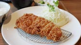 topped : Tonkatsu a Japanese dish which consists of a breaded, deep-fried pork cutlet served with shredded cabbage miso soup and bowl of rice. Stock Footage