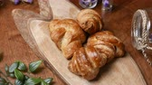 kruvasan : Fresh croissant a flaky, viennoiserie pastry on wooden board.