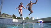 yüzme : Slow Motion Couple Jumping Into Swimming Pool Holding Hands