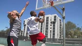 dunking : Two Basketball Players Playing One on One Outside and Scoring
