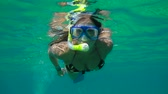 Young woman snorkeling in a tropical sea