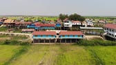 сок : 4k footage Rice fields from above on a windy day revealing traditionnal school painted blue