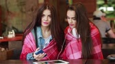 встреча : Two young and beautiful girl sitting at the table listening to music with a smartphone Стоковые видеозаписи