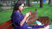 Woman sits on the bench and using smartphone over background the park. Dostupné videozáznamy
