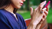 sentar se : Woman sits on the bench and using smartphone. Close view