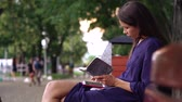 Young woman dressed casually works on a bench in the park. Dostupné videozáznamy