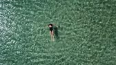 Girl in a black swimsuit swims in the sea. Dostupné videozáznamy