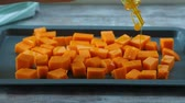 estanho : Chopped pumpkin being drizzled with olive oil before baking on a tin. Female hands