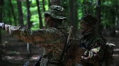 caqui : Guerilla warriors squad commander instructing his fighters in the forest bushes. War battlefield maneuvers training.