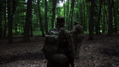 caqui : Guerilla partisan warriors walking in forest ambush carrying their guns. War battlefield maneuvers training.